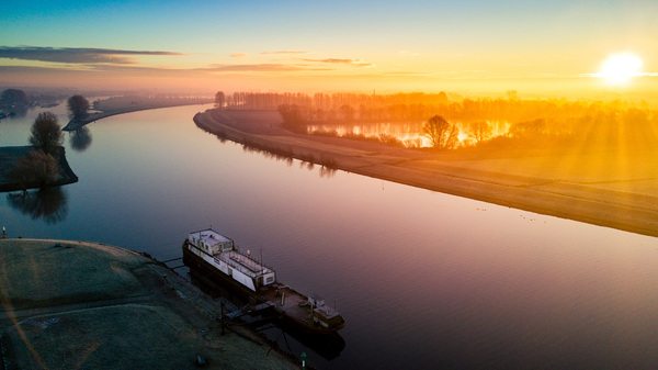 Wijk bij Duurstede. 8:45.  Zonsopkomst net buiten de haven met uitzicht op de Rijn. Mooi om te zien hoe de zonnestralen door de lage bomen worden geaccentueerd. #buienradar