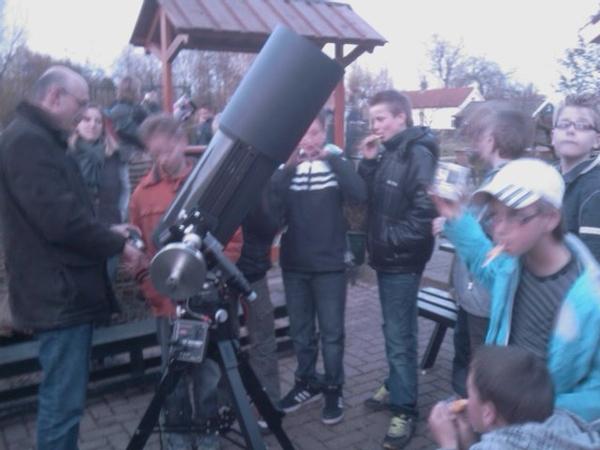 Paul vertelt de kinderen hoe de telescoop werkt. -