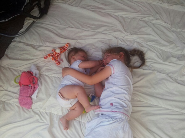 Dochters liggen heerlijk op een deken buiten bij opa. Wat zijn ze lief zo. Maar soms.....