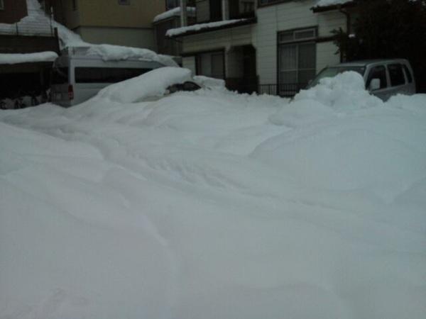 完全に埋もれきってるアパートの駐車場(笑)  一軒家の皆様と違って、車の所有者さん完全に雪かき諦めてるwww