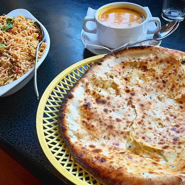 De Indiase en Pakistaanse keuken lopen op heel veel plekken in de wereld dwars door elkaar heen. Vaak worden zaken die door Pakistani gerund worden ook Indiaas genoemd, omdat dat beter verkoopt en staat er min of meer hetzelfde op de kaart: Britse adaptaties van eeuwenoude dissen van voor de tijd dat beide landen onder Brits Indië vielen. Uiteraard zijn er overeenkomsten tussen beide keukens en grote verschillen. Pakistaans is de peshawari naan ofwel het flatbread uit Peshawar: zoet en goed geschikt als balans bij veel kruidigheid op tafel. Of je geniet los van de met kokos en amandel gevulde naan, als banket. Ik at deze geweldige peshawari naan bij Sangam op de Vierambachtsstraat, een klein snackbar-achtig restaurant waar veel afgehaald en bezorgd wordt. Je eten staat binnen no time op tafel. Andere aanraders zijn hun uitgebreide vitrine met zoetigheden, de dal soep en zijdezachte biryani. Hier kom ik snel terug.  #pakistan #pakistanfood #india #indianfood #naan #peshawarinaan #debuikvanrotterdam #rotterdamwest #vierambachtstraat